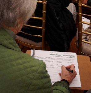 Older woman in green jacket signs a petition on her lap