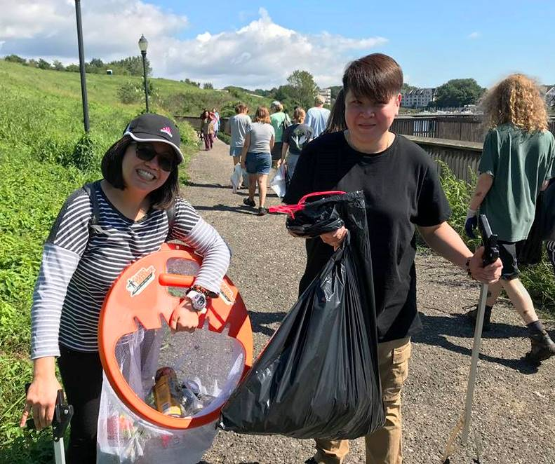 A woman and teen son hold trash bags and orange cleanup tools