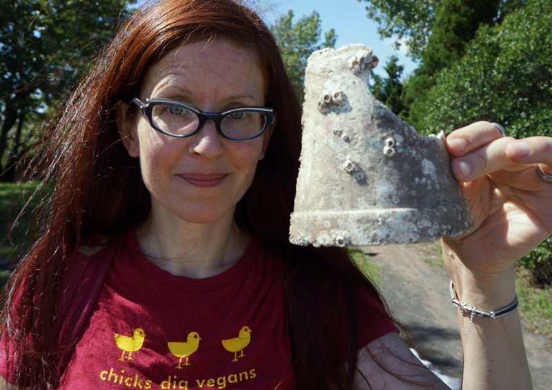 Red-haired woman in red shirt and glasses holds up a broken styrofoam cup with barnacles on it