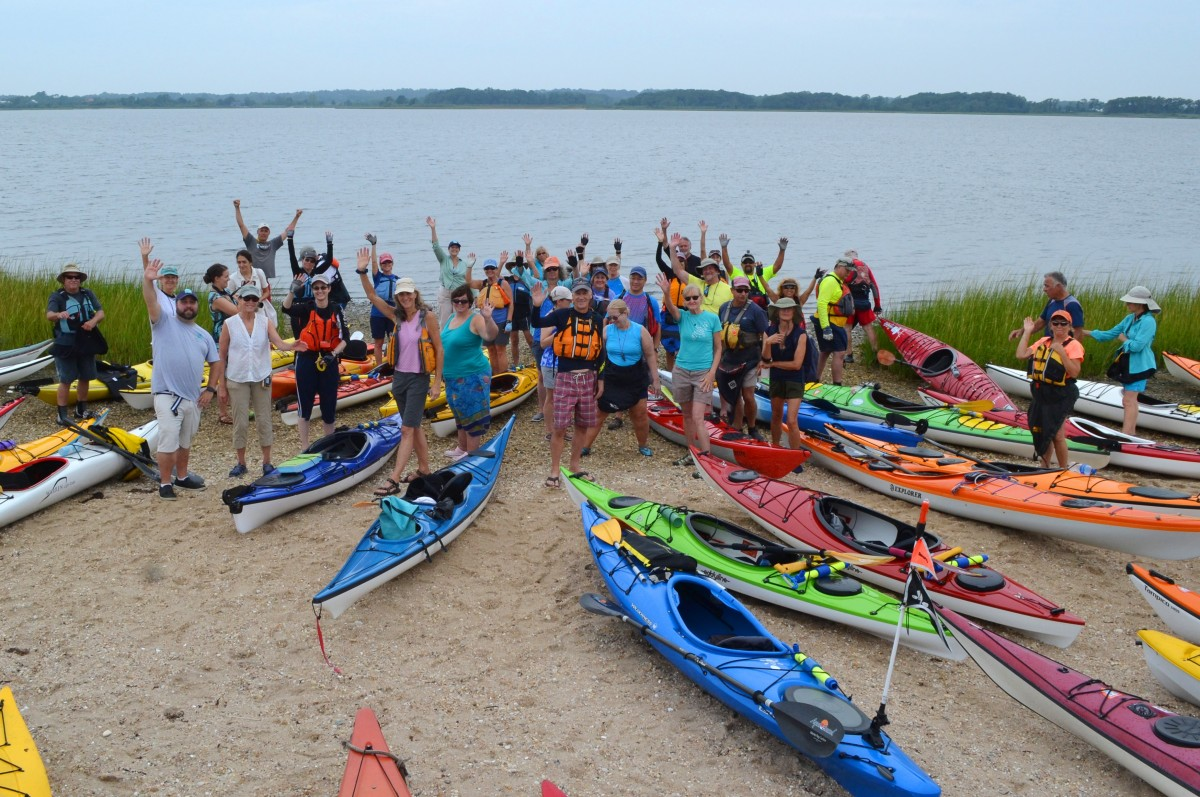 30 people in colorful gear wave on a beach with kayaks