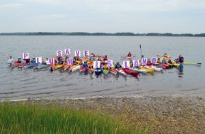 """People in colorful kayaks float while holding up signs that spell out """"SAVE PLUM ISLAND"""""""