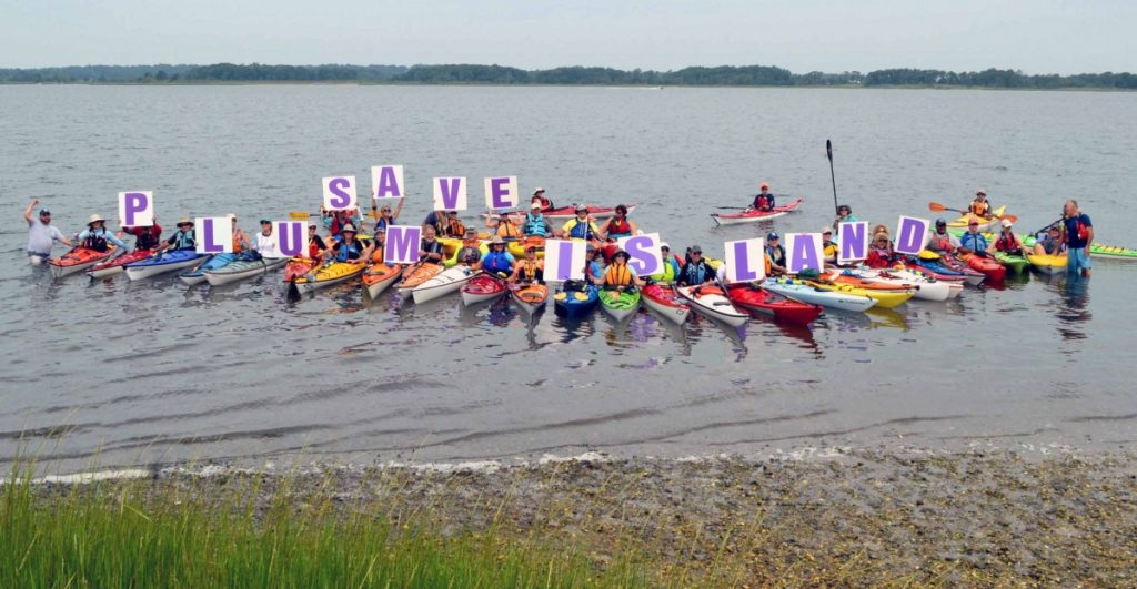 "People in colorful kayaks hold up signs spelling out ""SAVE PLUM ISLAND"""