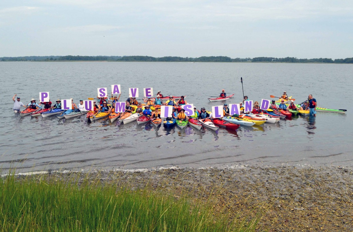 "People in colorful kayaks float while holding up signs that spell out ""SAVE PLUM ISLAND"""