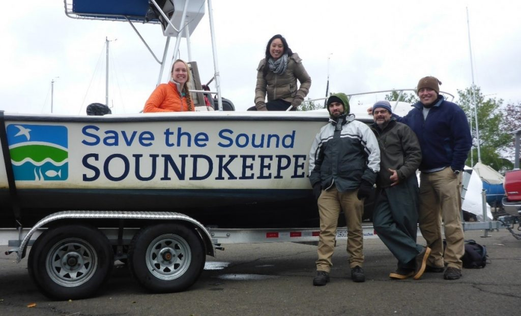 """A boat labeled """"Save the Sound Soundkeeper"""" on a trailer. Two women are sitting in the boat, and three men are standing next to it."""