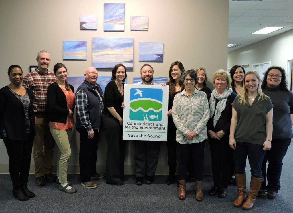 A dozen staff members pose with a CFE/Save the Sound logo sign in the office