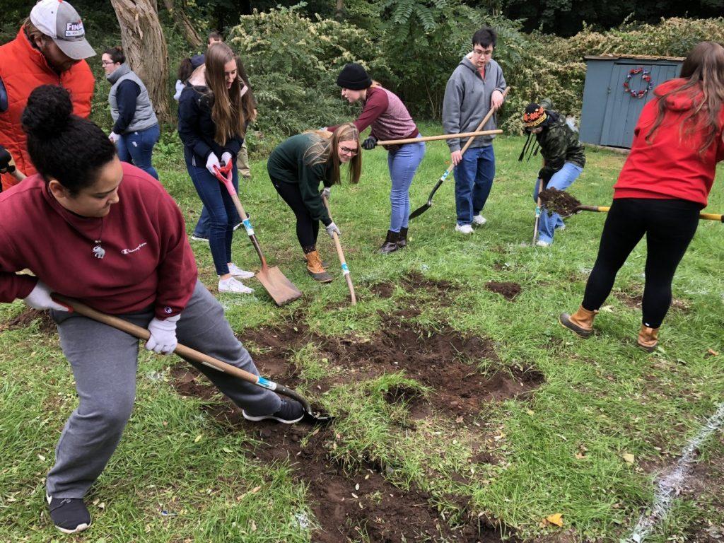 A diverse group of teenagers shovels dirt to start a rain garden