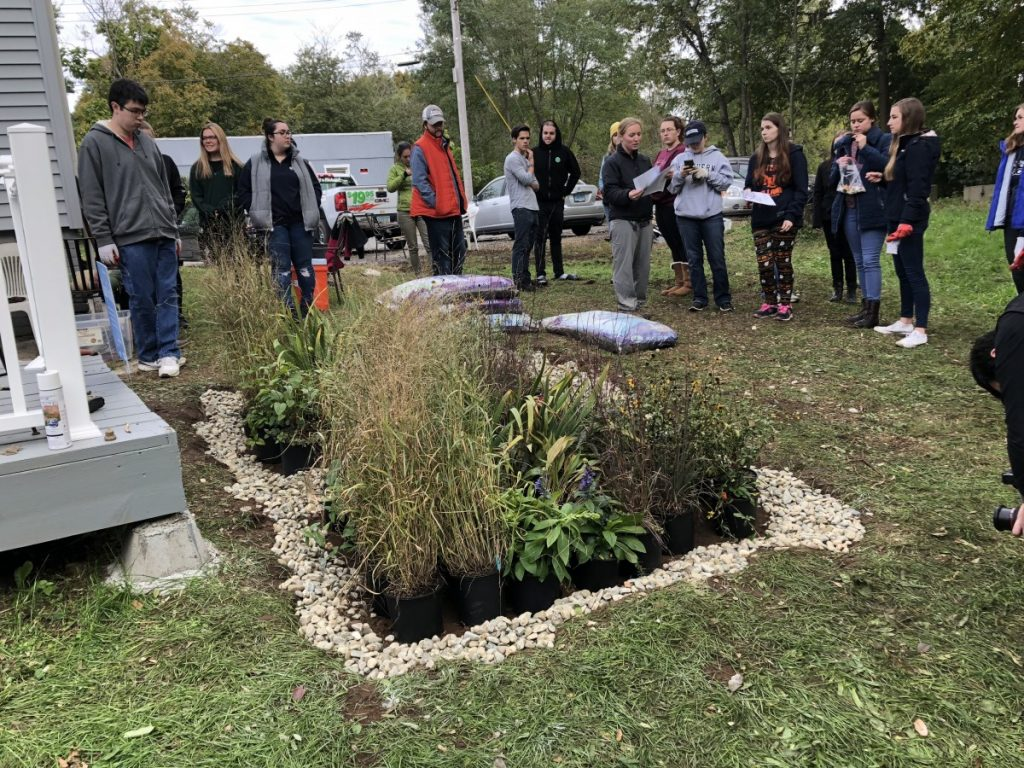 Student volunteers stand around a rain garden they just built