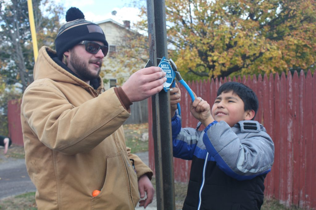 Bearded man in a hat and elementary school kid attach trail marker to street sign