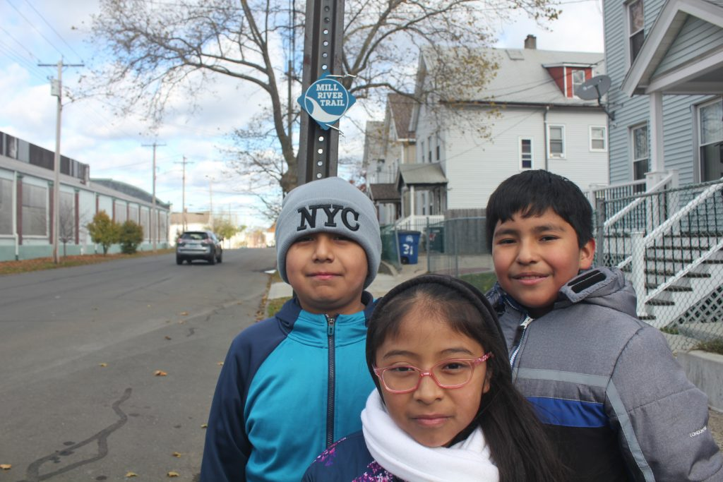 Three Latinx children in winter clothing stand on a sidewalk with a Mill River Trail marker