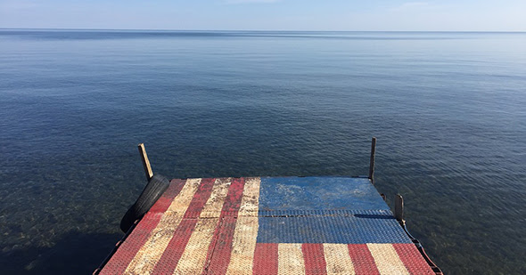 Dock with flag pattern and water to horizon