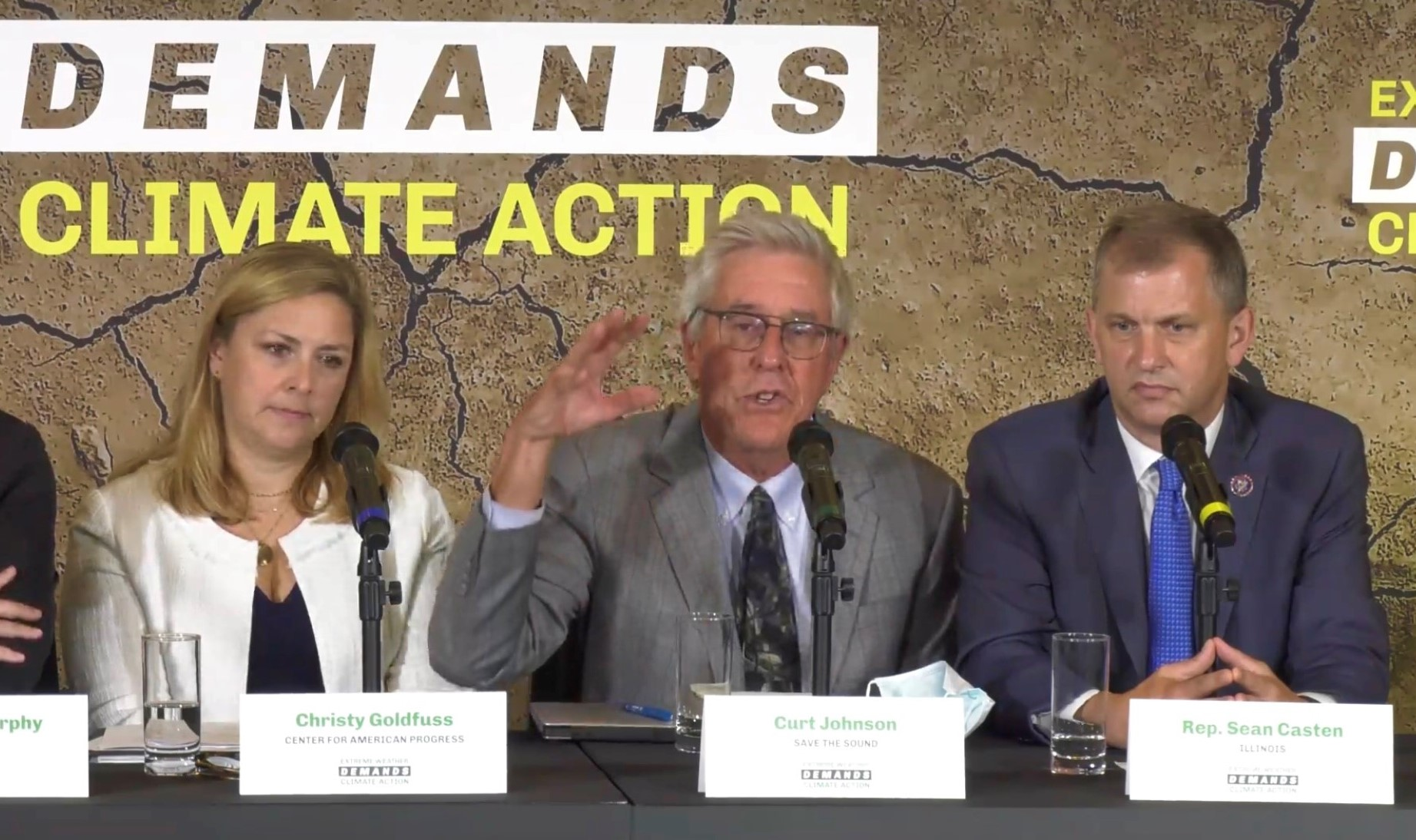 """Save the Sound president Curt Johnson, flanked by two people, gesticulating in front of a sign that says """"demands climate action"""""""