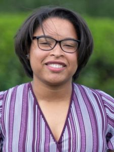 headshot of Leticia, a smiling Black woman in a purple shirt and glasses